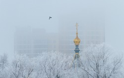 The dome of the Orthodox Church is visible from behind trees covered with frost. High rise apartment building in the background in the fog.