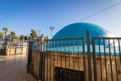The dome painted blue above the building inside is the tomb of Rabbi Shimon Bar Yochai in Meron-Israel