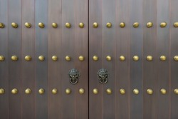 The door and knockers of Chinese temple. Ancient Asian door from temple. Chinese door. Oriental design of door of palace hall in Forbidden City.