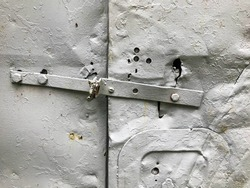 the door is metal, painted in gray paint. a builder's booth texture with metal inserts, hooks. metal sheet with holes, damage, rust and corrosion.