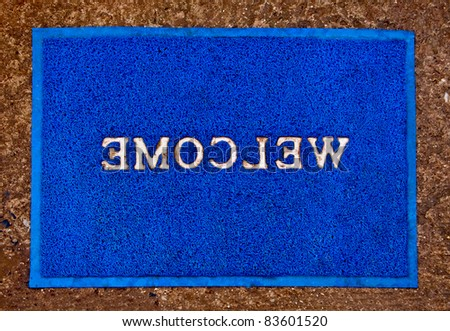 The Doormat of welcome text on floor background