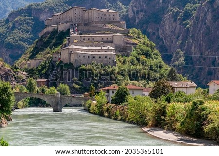 The Dora Baltea river flows under the hill of Bard's Fort, Valle d'Aosta, Italy Stock fotó ©