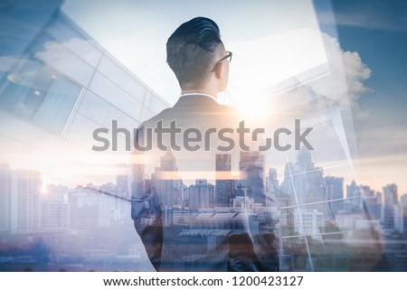 The double exposure image of the business man standing back during sunrise overlay with cityscape image. The concept of modern life, business, city life and internet of things.