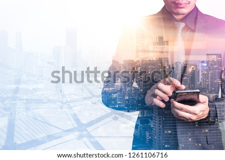 The double exposure image of the business man using a smartphone during sunrise overlay with cityscape image. The concept of modern life, business, city life and internet of things. #1261106716