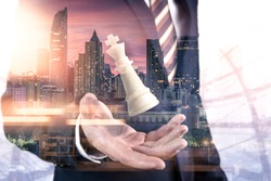 The double exposure image of the businessman hold a chess king on hand overlay with cityscape image. the concept of strategic, planning, management, intelligence and education.