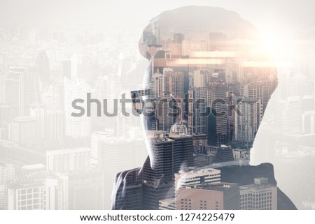 The double exposure image of the businessman standing back during sunrise overlay with cityscape image. The concept of modern life, business, city life and internet of things. #1274225479