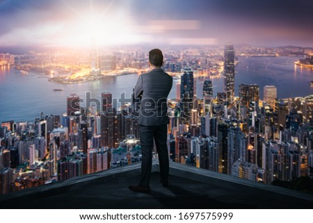 The double exposure image of the businessman standing back during sunrise overlay with cityscape image. The concept of modern life, business, city life and internet of things.