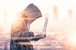 The double exposure image of the hacker using a laptop overlay with binary code image and blurred cityscape is backdrop. the concept of cyber attack, virus, malware, and cyber security.