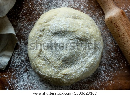 The dough is sprinkled with flour on a wooden background.