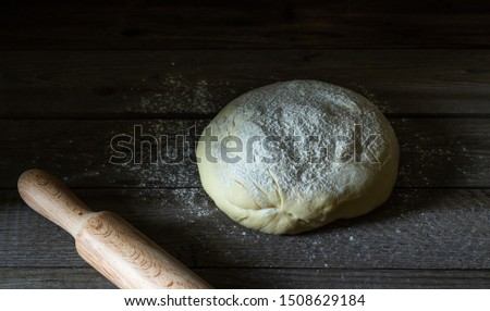 The dough is sprinkled with flour on a wooden background. Pastries. Pie. Pizza. Recipes