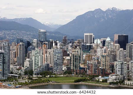 The downtown highrise area of Vancouver, British Columbia, Canada, fronted by a park and the shoreline of False Creek, backed by the treed and snow capped coastal mountains.