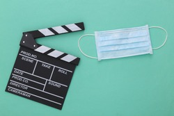 The downturn in the entertainment industry during covid-19. Movie clapper board with medical mask on a mint color background. Filmmaking. Top view