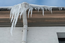 The drainpipes are covered with ice and snow. After a heavy snowstorm, the city is covered with snow and ice. There are many icicles on the facade of the building. Ice on sidewalks and roads.
