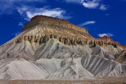 the dramatically-eroded cliffs  of mount garfield against a blue sky, grand junction, colorado