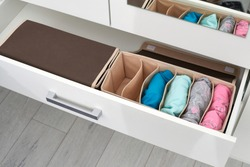 The drawer is divided into cells of different sizes, for separate storage of linen and fabrics. Home storage system for storing clothes. Folding boxes in a set have different shapes.