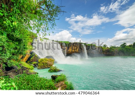 Stock Photo The Dray Nur Waterfall on the Serepok River among green trees at the Tay Nguyen (the Central Highlands) in Dak Lak Province (Daklak) of Vietnam. Amazing summer landscape with azure pond and blue sky.