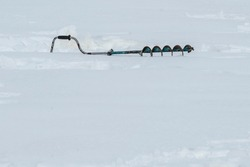 The drill for drilling holes in the ice lies on the snow. Advertising products for winter fishing with a place for text.