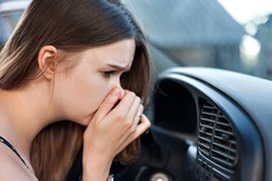 the driver held his nose from the bad smell , air conditioner heating, the concept of faulty air conditioners, bad smell and car, refilling of refrigerant in the air conditioner
