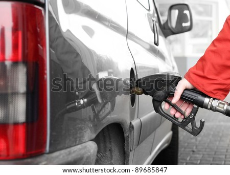 The driver pumping gasoline at the gas station.
