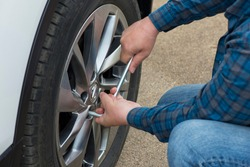 The driver's hand with the key tightens the bolts on the wheel of the car