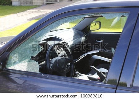 The driver's window has been smashed and the interior vandalized/Auto Theft/A vandalized car in an urban setting