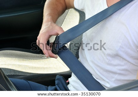 The driver sits in the car and lays down the safety-belt