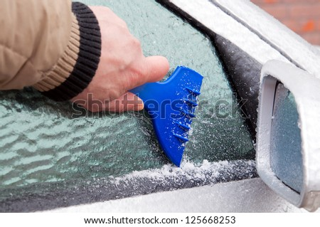 The driver tries to clean auto glass iced