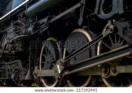 stock-photo-the-driving-wheels-of-a-steam-locomotive-as-it-passes-close-at-hand-on-the-tracks-217292941.jpg