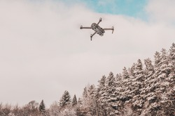 The drone flies in the winter above the forest and shoots landscape videos.