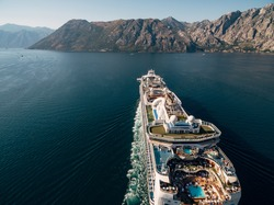 The drone flies over the chicken liner. A close-up of the upper deck of a huge liner. Swimming pool on the ship and many tourists. Sails in the Bay of Kotor in Montenegro, next to the mountains.