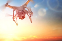 The drone in the  sunset sky. Close up of quadrocopter outdoors.