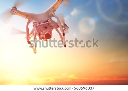 Shutterstock The drone in the  sunset sky. Close up of quadrocopter outdoors.