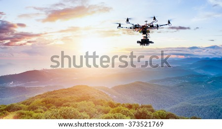 The drone with the professional camera takes pictures of the misty mountains at sunset. Uav drone copter flying with digital camera. Hexacopter drone with high resolution digital camera on the sky.