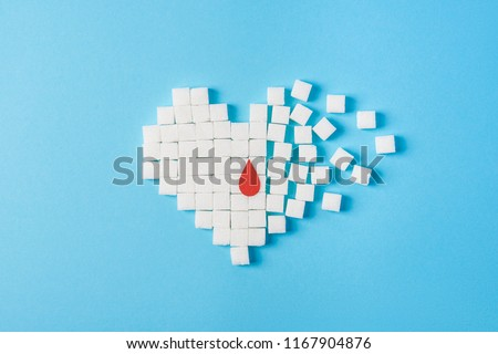 the drop of blood on broken heart made of pure white cubes of sugar isolated on blue background, World diabetes day, November 14