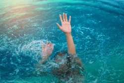 The drowning hand stretched out over the surface for help.