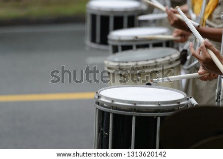 The drummer is drumming snare drum (side drum) in a marching band in the parade.