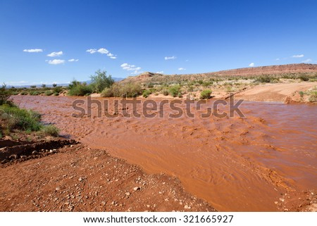 The dry wash is flooded with muddy water after rain storm in Southern Utah desert. The water blocked the dirt road and it was impassable. Stock photo ©