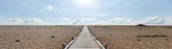The Dungeness headland in Kent is the only area in Britain that could be considered desert.  This windswept and forlorn location has this wooden plank path leading across the shingle to the sea.