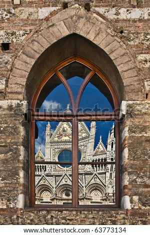The Duomo (Cathedral) of Siena reflecting in gothic window, Tuscany, Italy
