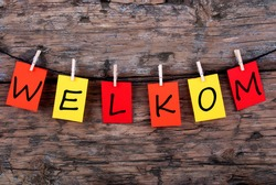 The Dutch Word Welkom, which means Welcome, on Notes Hanging on a Line on Wooden Background