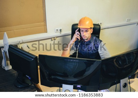 The duty engineer in an orange helmet is talking on the phone in front of several monitors. Monitoring department at the nuclear power plant. A professional specialist works on the computer #1186353883