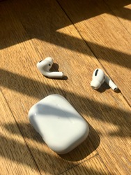 The earphones on the wooden background. Airpods Pro. Active noise cancellation with sweat and water resistance and a customizable fit · AirPods Pro. · Sound that cuts out the noise.