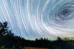 The Earth rotation as seen in the night sky with the star trails. An awe scenery in the outdoors with the forest, the trees and the stars glowing in the distance. A dreamlike and colorful scenery