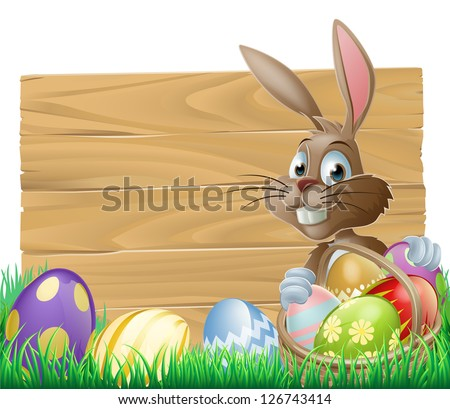 The Easter bunny with a basket of Easter eggs with more Easter eggs around him by a wood sign board