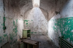 The Eastern State Penitentiary a former American prison in Philadelphia, Pennsylvania. The view of an abandoned  decaying cell with furniture and a single glass skylight, representing the