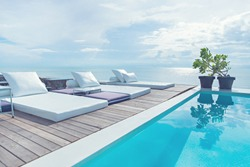 The edge Luxury swimming pool with white fashion deckchairs on the beach., Exterior design.
