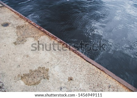 The edge of the old concrete pier with a rusty iron edging. Diagonal in the frame. Blue water with ripples and a reflection of the sky.
