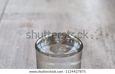 The effect of surface tension, pure water in a glass cup forms a dome. Neutral wood background in soft focus.