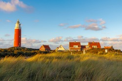 The Eierland Lighthouse on the northernmost tip of the Dutch island of Texel during the sunset, Red lighthouse tower on the dunes with marram grass and blue sky background, North Holland, Netherlands.