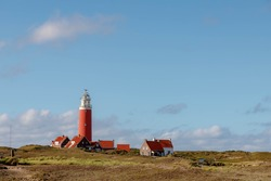 The Eierland Lighthouse on the northernmost top of the Dutch island of Texel, Red lighthouse tower on the dunes with european marram grass and blue sky as background, North Holland, Netherlands.